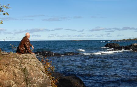 Retired senior sits on a rocky ledge overlooking Lake Superior on the Keweenaw Peninsula   He is staring at the blue horizon in a brown leather coat  photo
