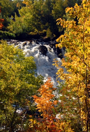 eagle falls: Beautiful Eagle River Falls, full from recent rain, rushes over the rocky cliff and falls to the river below   Autumn foliage frames falls  Stock Photo