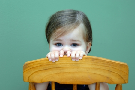 Toddler rests her head against her hands as she leans over the back of a wooden chair   Walls behind child are green  Stock Photo - 14824166
