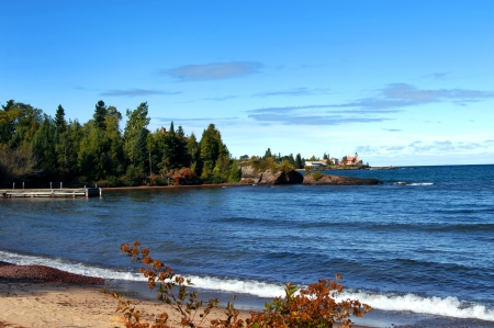 Rustic wooden pier fronts image of Lake Superior, Michigan   Background shows Eagle Harbor Lighthouse and Keweenaw Peninsula