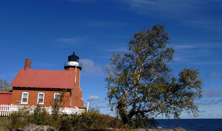 Eagle Harbor Lighthouse stands guard over Lake Superior in Upper Peninsula, Michigan   Brick architecture with black domed light has keeper