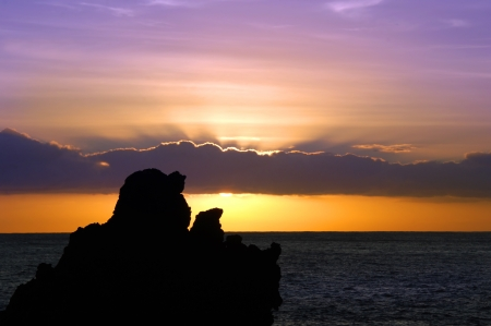 Rising sun colors the clouds and sky purple   Sea stacks of black lava are silhouetted by color on Laupahoehoe Beach Park on the Big Island of Hawaii  photo