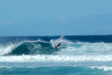 Sailboarder glides across the crest of a large wave off the island of Kauai                              photo