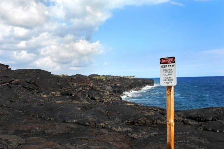 danger: Danger, keep away, is posted at cliffs edge.  Hawaii Volcanoes National Park warns visitors of the dangers of the lava hardened cliffs formed when Mauna Ulu erupted.   Stock Photo
