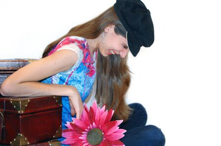 knocked over: Teenager gets her tickle box knocked over, and laughs hillariously.  She is leaning on a set of old suitcases and holding a hot pink daisy.