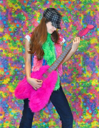 unsmiling: Modern teen grooves to the music with a tye dye background in smudged circles and hot colors.  She is wearing bright colored scarves and pretending to play a hot pink funky guitar.