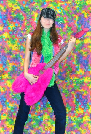 grooves: Female teen holds a stuffed, furry, pretend guitar and grooves to the 70s music.  She is standing in front of a tye-dye background.