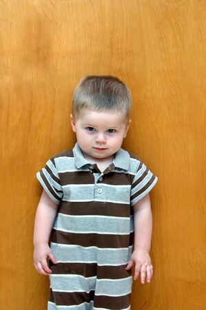 Little boy stands against a wooden door.  His expression is one of pure guilt, so he does a