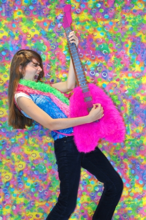 Getting into the part, teen plays wildly on the guitar, grimacing to the 70s disco beat.  Pink guitar with tye-dye background. photo
