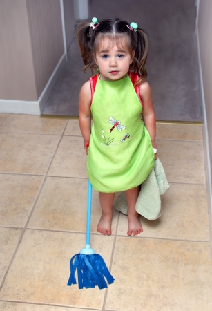 housecleaning: All hands on deck!  This little girl is ready and willing to help her mother with household chores.  She is wearing her apron, holding her dusting rag and weilding her mop. Stock Photo