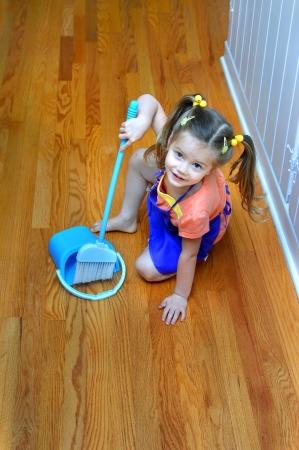 Bereid helper leert huishoudelijke taken te doen. Ze houdt een blauwe bezem en vegen in een blauwe blik. Meisje glimlacht en draagt een paarse schort.