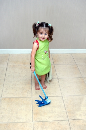 Adorable little girl pushes her mop back and forth cleaning the floors.  She is learning household chores from her mom.  She is wearing a green apron and holding a blue, play, mop.