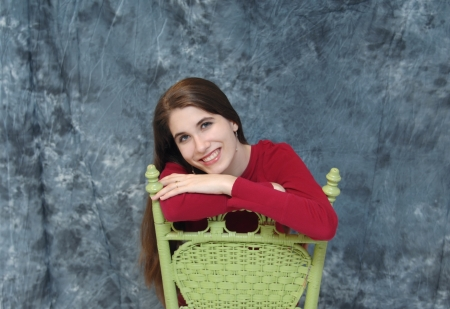 Female teen sits on a green, wooden chair backwards.  She rests her arms on the chair and smiles.  Image has grey blurred background. photo