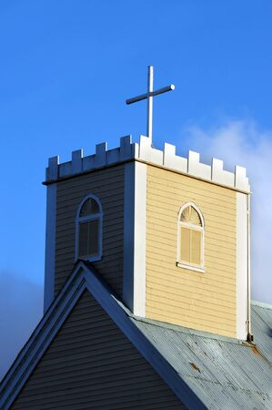 Historic Imiola Church on the Big Island of Hawaii, has cross topping its square built steeple.  Original tin roof and quaint architecture makes this aging church an architectural gem. Stock Photo - 14831987
