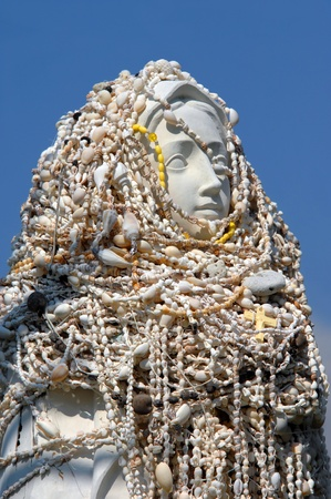 of homage: Statue of Virgin Mary is covered in shell necklaces at St. Benedicts Painted Church on the Big Island of Hawaii.  Necklaces show sign of worship, homage and respect.