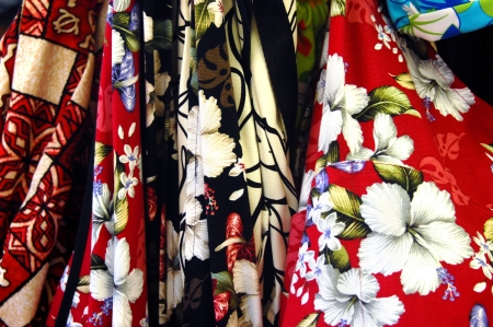 depict: Brightly colored fabrics depict hibiscus blooms.  Souvenier shirts are for sale at every shop on the Hawaiian islands.