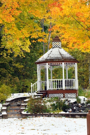 Bright yellow leaves surround gazebo in Upper Peninsula, Michigan   Lanscaping includes steps and stones and snow covered ground  photo