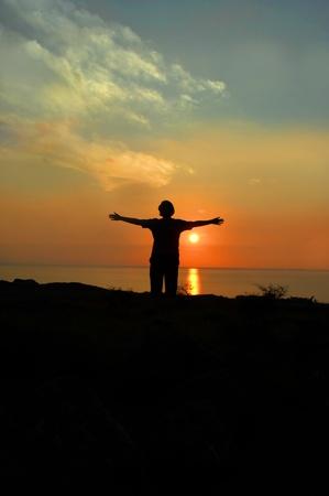 mujer mirando el horizonte: Visitante se encuentra con los brazos diciendo adi�s a la Isla Grande de Hawai. El sol se pone al final del d�a ya que su viaje est� tambi�n terminando.