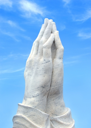 lifted hands: Marble hands are folded in a prayer of supplication   Hands are surrounded by blue sky and wispy clouds