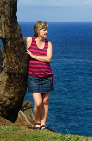Woman stands on cliffs edge admiring the view of the northern coast of the Big Island of Hawaii   She is wearing a denim skirt and striped top  Stock fotó
