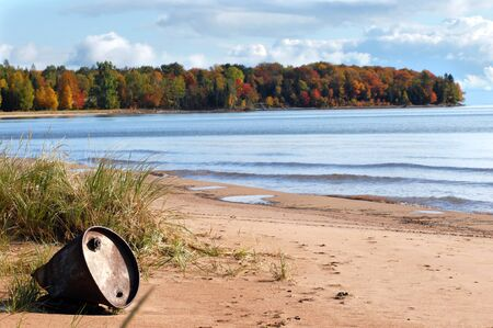 upper peninsula: Beautiful landscape is ruined by discarded industrial barrel washed ashore   Lake Superior in Upper Peninsula, Michigan is alive with Autumn color  Stock Photo