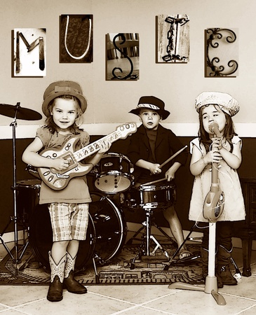 child singing: Three siblings pretend to be a music band.  They are playing instruments and one is singing.  The letters M, U, S, I, C is posted on the wall.  Youngest member is singing. Stock Photo