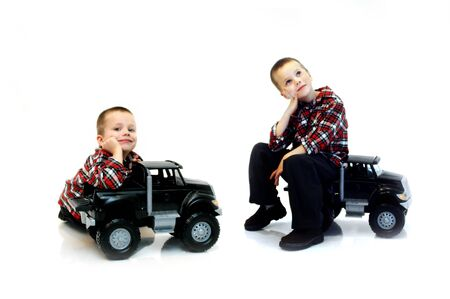 imagining: Little boy dreams of one day driving and owning a monster truck.  He is leaning and sitting on his black toy truck and imagining it a whole lot bigger.