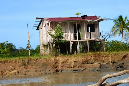costa rican: Costa Rican home sits on river bank and is elevated for the rainy season.  Tin roof is in disrepair and home looks deserted. Stock Photo