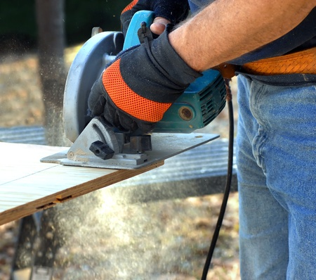 Man holds circular saw and cuts plywood on construction site.  Shot shows hands and tool and saw dust flying.
