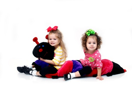extra large: Two sisters wrestle with an extra large stuffed catepillar.  The two sisters are sitting on the toy and having fun.