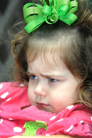 slumped: Little girl expresses her extreme displeasure.  He brow is furrowed and she has slumped down in an obstinate position.