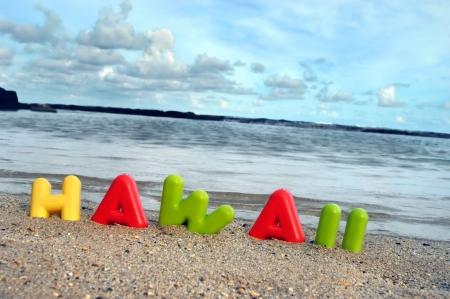 Día termina el otro día en el paraíso con los niños. Letras coloridas ortografía Hawaii están enterrados en la arena en una playa de arrecife protegido en el lado de barlovento de Oahua. Foto de archivo