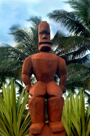 Large wooden tiki stands guard in garden setting.  Features are fierce and depicts warrior stance. photo