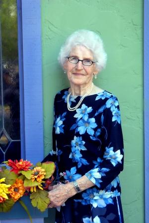 Classy ältere Frau arrangiert Blumen in einer Fenster-Box vor ihrem Geschenkeladen. Standard-Bild - 14845289