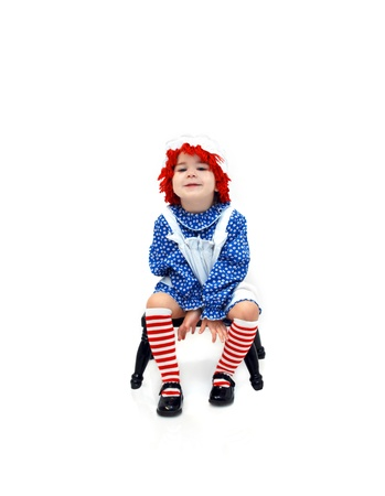 raggedy: Old fashioned rag doll costume is worn by a cute little three years old.  She is sitting on a milking stool and grinning from ear to ear. Stock Photo