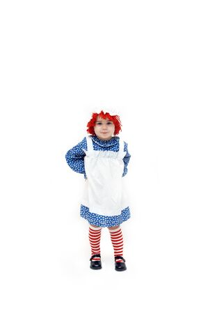 raggedy: Old fashioned Raggedy Ann style costume is worn by a cute little girl with a cute little smirk.  Complete with apron and striped socks, her hair is red yarn and topped with a white mop hat.