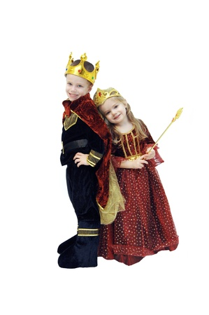 Two small children dressup in their Halloween costumes.  One is dressed as a king and the other a queen.  Costumes are complete with crowns and sceptor.
