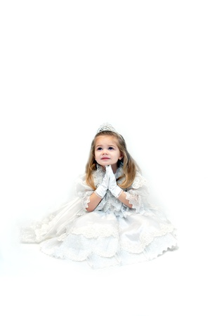 Little girl folds her hands in prayer.  She is sitting in an all white room and wearing an all white pageant dress and crown. Stock Photo