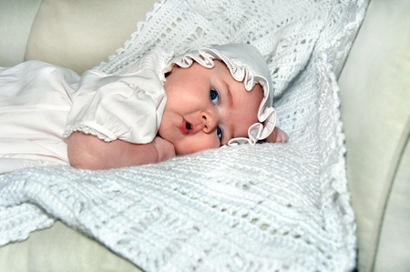 Tiny newborn is wearing a dress and bonnet.  She is laying on her tummy on a shawl on living room couch.  Her eyes are open and her mouth is bow shaped. Stock Photo - 14846693