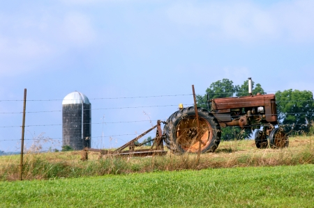 bush hog: Vintage tractor and mower sit idle besides a barbed wire fence.  Silo and blue sky fill background.