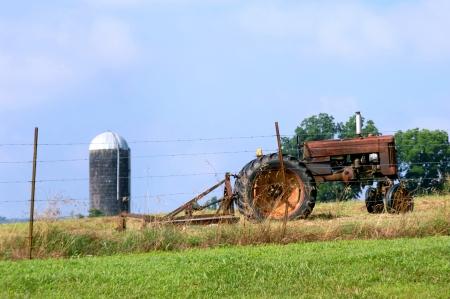 bush hog: Vintage tractor y la segadora fuera de uso, adem�s de una cerca de alambre de p�as. Silo y cielo azul rellenos de fondo.