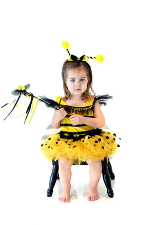 Little girl is dressed up as a bumble bee.  She is holding a special bumble bee wand and ready to work her magic on the flower world. photo