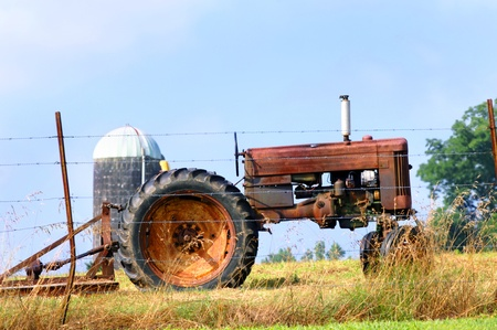 bush hog: A relic of farming is parked at the fence row to be sold.  Tractor and bushhog stands idle and rusting.  A lone silo stands in the background.
