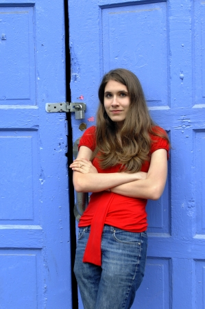 locked: Young teen leans against a vivid blue door.  She is wearing jeans and a red top and is solemn.