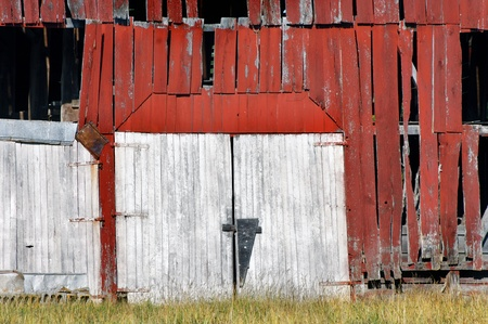 Double barn doors are boarded shut and historic building is abandoned.  Red, wooden, weathered and overgrown, this barn is derelict and dejected. photo