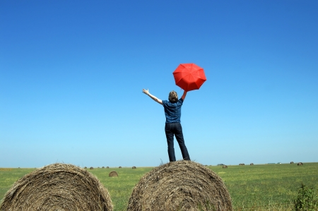 wide open spaces: Woman stands on top of round hay bales on a prairie in Kansas.  She is embracing the wide open spaces and the state that she loves.  She is holding a red umbrella and waving it.