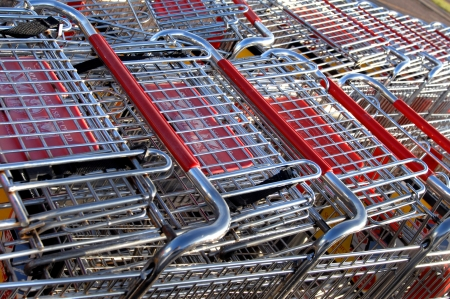 shopping buggy: Large group of shopping buggies are stacked and ready for customers to fill with market goods.  Silver buggies with red seat guards for safety.