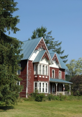 gabled house: Gingerbread style home has been reroofed in an effort to preserve this old homestead.  Red paint is peeling from the sides and eaves home this red, blue and white home.