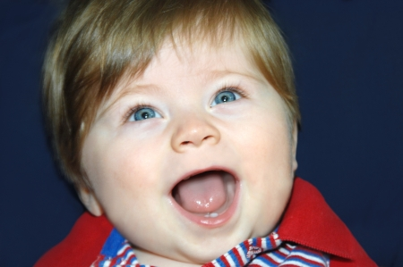 Baby has his mouth wide open and his eyes are sparkling.  Closeup of his face shows two small teeth in his open mouth. photo