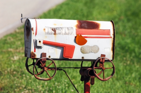 unopen: Metaphoric mailbox shows this family has moved.  Handmade mailbox design depicts a moving wagon.  Abandoned by family, mailbox sits rusting and derelict on iron post.